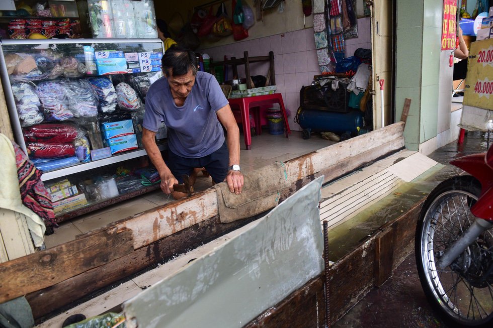 A man uses wooden planks to keep water from flowing into his house. Photo: Quang Dinh / Tuoi Tre