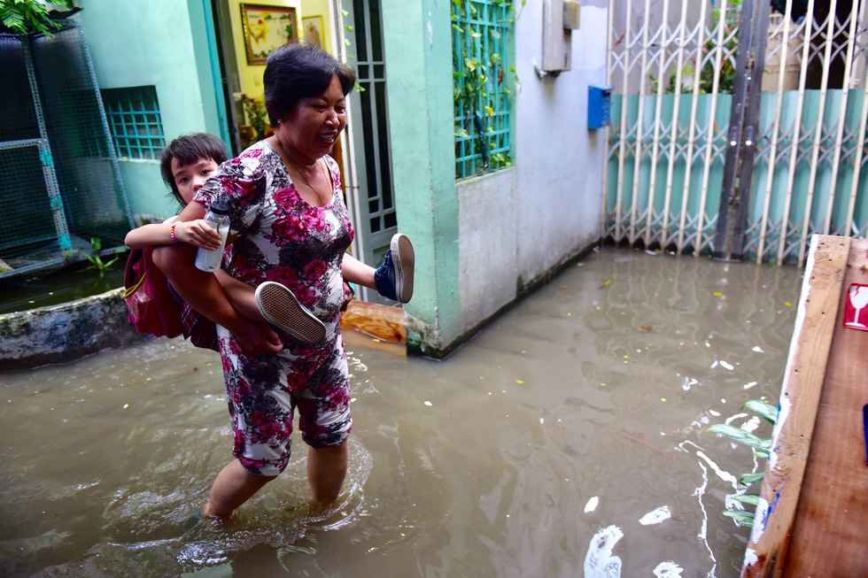 A woman carries a child along a flooded alley in District 7. Photo: Quang Dinh / Tuoi Tre