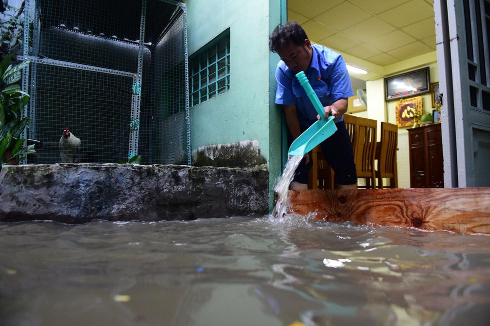 A man scoops water out of his home. Photo: Quang Dinh / Tuoi Tre