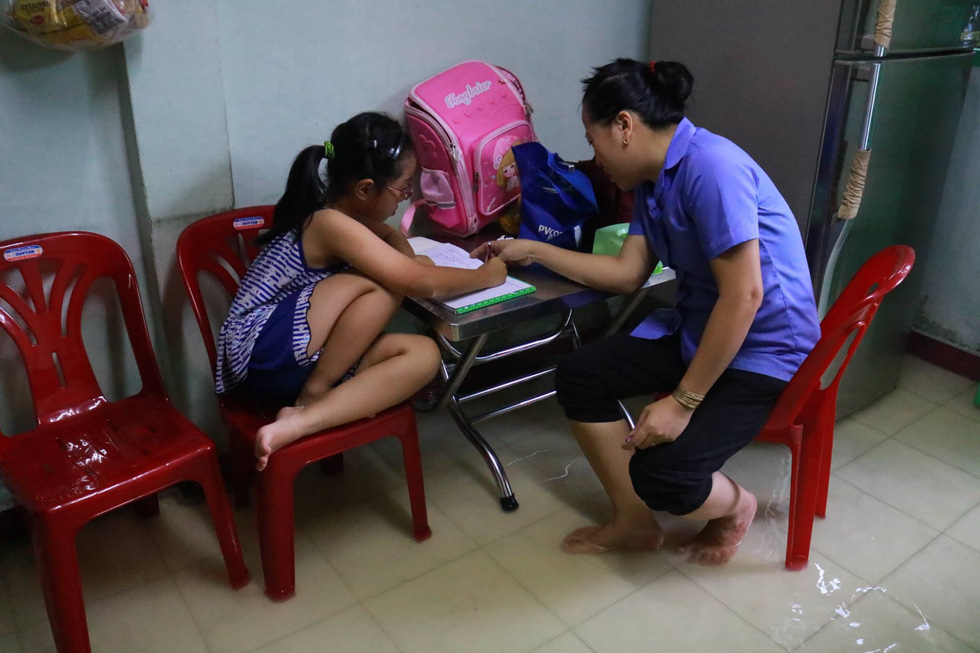 A woman helps her daughter with her homework inside their flooded house in District 4. Photo: Ngoc Phuong / Tuoi Tre