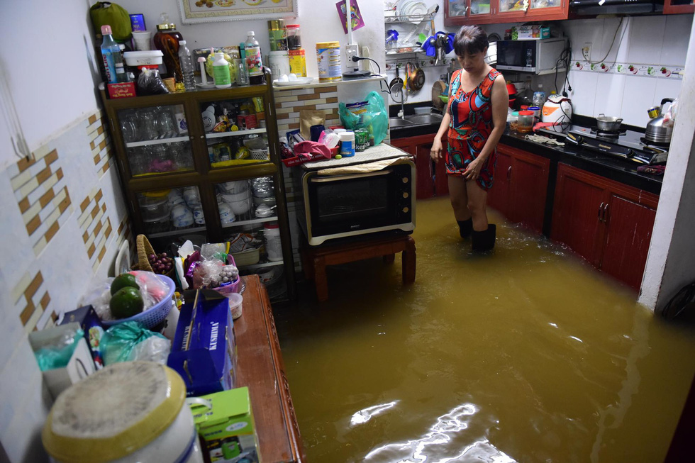 A woman stands inside her flooded kitchen. Photo: Quang Dinh / Tuoi Tre