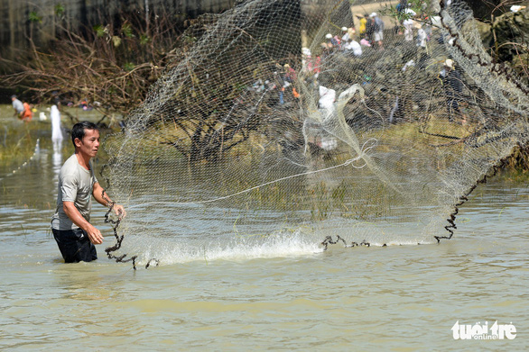 A man throws a fishing net to catch fish near the Tri An hydropower dam in Dong Nai Province, Vietnam on September 30, 2019. Photo: A Loc / Tuoi Tre