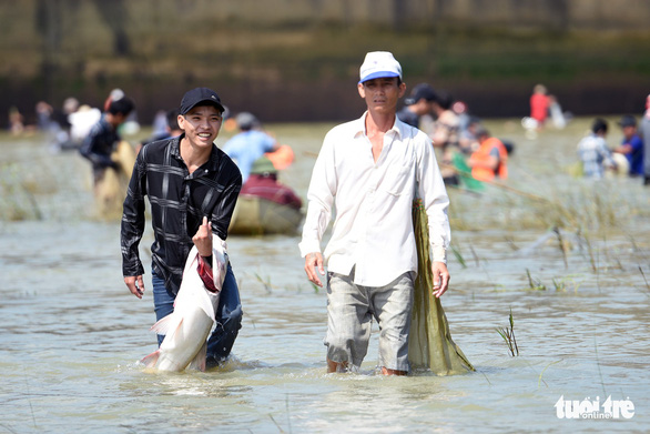 A man smiles as he carries a freshly caught fish near the Tri An hydropower dam in Dong Nai Province, Vietnam on September 30, 2019. Photo: A Loc / Tuoi Tre
