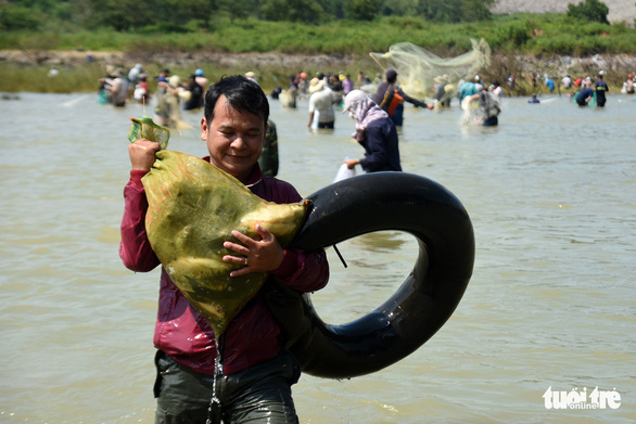 A man carries freshly caught fish in a bag near the Tri An hydropower dam in Dong Nai Province, Vietnam on September 30, 2019. Photo: A Loc / Tuoi Tre
