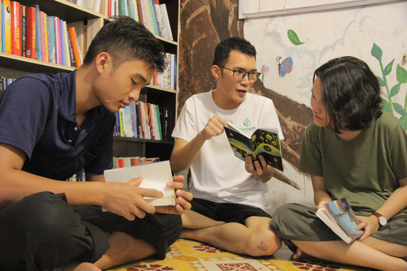 Hoang Quy Binh (mid) and two visitors at D Free Book. Photo: Ha Thanh / Tuoi Tre