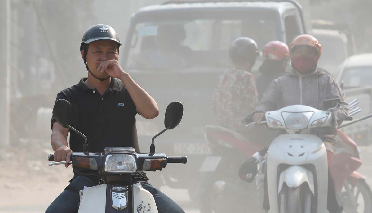 A man covers his nose as he drives through an air polluted street in Hanoi, Vietnam October 1, 2019. Photo: Reuters