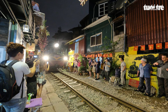 Visitors take photos next to the railway track in Hai Ba Trung District, Hanoi. Photo: Nam Tran / Tuoi Tre