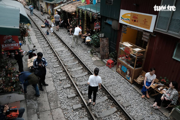 Visitors take photos on the railway track in Hai Ba Trung District, Hanoi. Photo: Nam Tran / Tuoi Tre