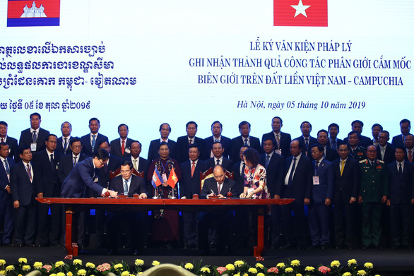 Cambodian Prime Minister Hun Sen (L) and Vietnamese Prime Minister Nguyen Xuan Phuc sign legal documents on bilateral land boundary demarcation in Hanoi on October 5, 2019. Photo: Nguyen Khanh / Tuoi Tre