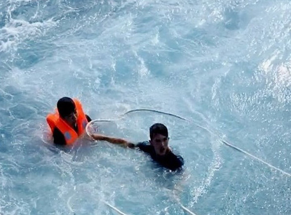 Tran Thanh Ron (right) struggles in sea water to rescue a fisherman in this still cut from a provided video