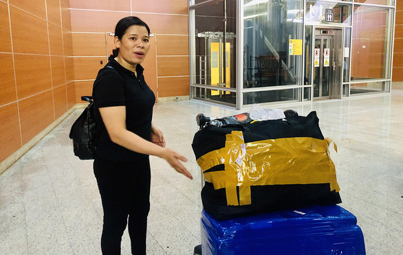 Le Thi Oanh carefully watches her luggage as well as the security staff at the airport hall in Moscow, Russia. Photo: Thao Thuong / Tuoi Tre
