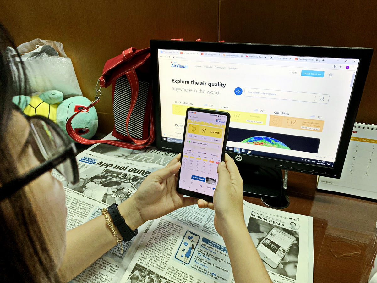 A young woman checks the AirVisual mobile app for air quality index in Hanoi in this photo taken on October 8, 2019. Photo: Tuan Son / Tuoi Tre News