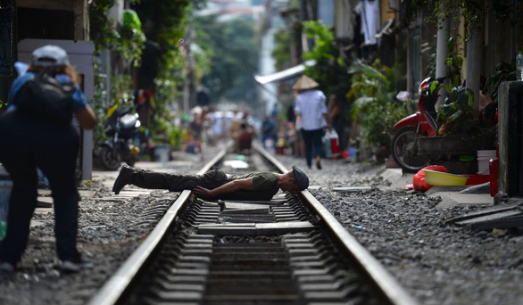 A tourist lies face-down across railway tracks in Hanoi for a photo shoot. Photo: AFP