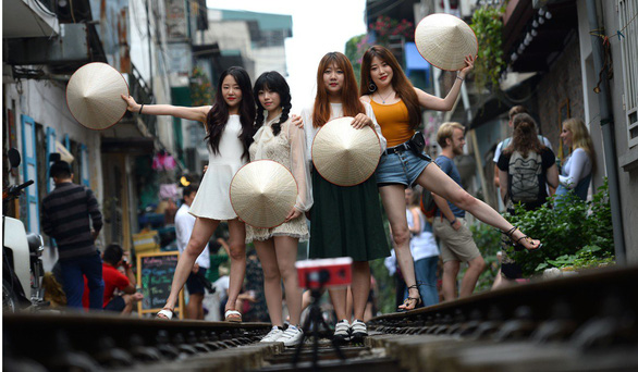 Tourists pose on railway tracks in Hanoi. Photo: AFP