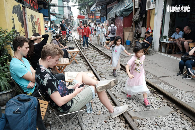 Visitors have drinks at cafés next to the railway track in Hai Ba Trung District, Hanoi. Photo: Nam Tran / Tuoi Tre