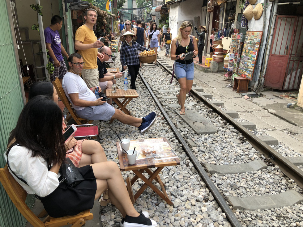 Visitors have drinks at cafés next to the railway track in Hanoi before the area was blocked in an attempt of local authorities to ensure public and traffic safety. Photo: Q.TH/ Tuoi Tre