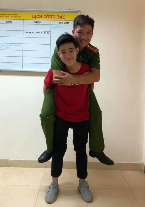 Nguyen Hoang Giang piggybacks firefighter Hoang as they pose for a photo during their meeting on October 11, 2019. Photo: Pham Thang / Tuoi Tre