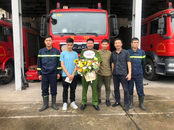 Nguyen Hoang Giang (blue T-shirt) and his father (third right) pose for a photo with officers at the firefighting department in Dong Da District, Hanoi, October 11, 2019 in this provided photo.