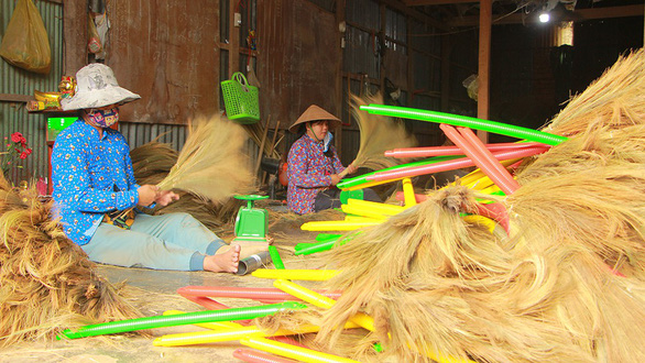 Two women make grass brooms at Nguyen Ngoc An's facility in the Mekong Delta province of An Giang. Photo: Chi Cong / Tuoi Tre