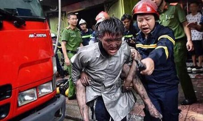 Firefighter Hoang piggybacks Nguyen Hoang Giang as they get out of a fire in Ba Dinh District, Hanoi, September 10, 2019 in this provided photo.