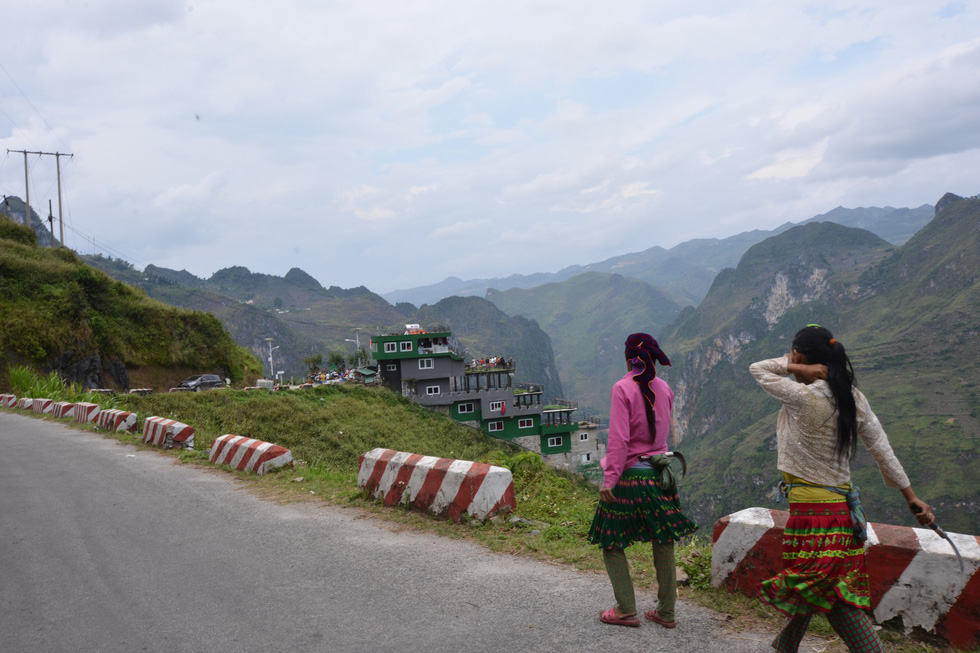 Two women walk on Ma Pi Leng mountain pass in Ha Giang Province, Vietnam, with the Ma Pi Leng Panorama building spotted afar. Photo: Vu Tuan / Tuoi Tre