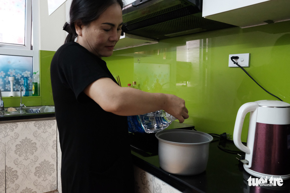 A woman uses bottled water for cooking. Photo: Mai Thuong / Tuoi Tre