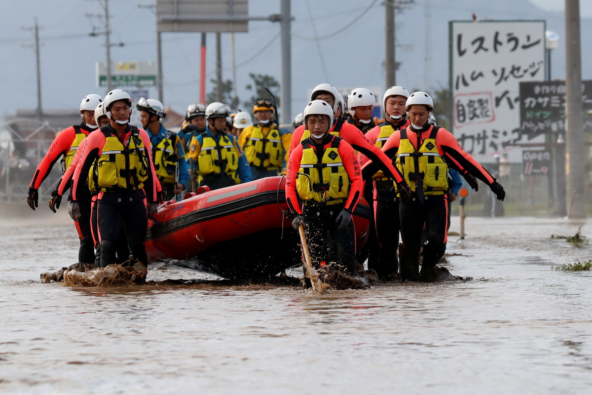 Rescue workers carry a rubber dinghy as they search a flooded area in the aftermath of Typhoon Hagibis, which caused severe floods at the Chikuma River in Nagano Prefecture, Japan, October 14, 2019. Photo: Reuters