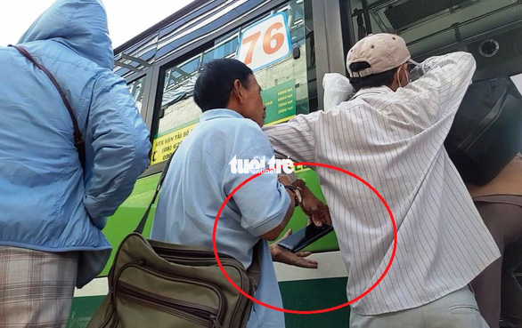 A pickpocket passes a stolen phone to his partner. Photo: Minh Hoa / Tuoi Tre
