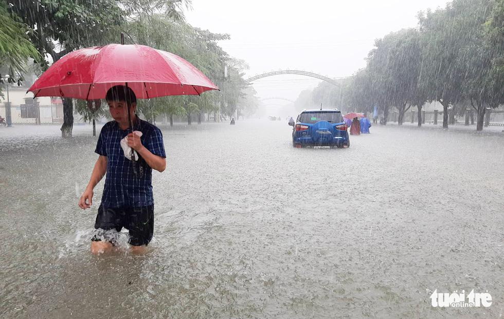 Residents travel amidst knee-deep rainwater in Vinh City.