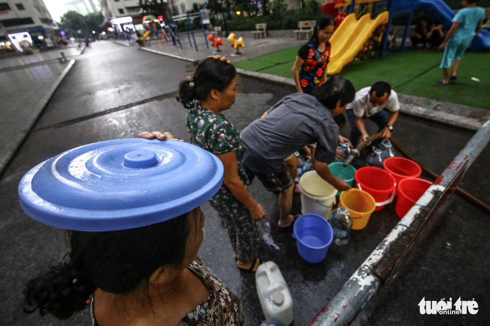 People queue for clean water in the rain in Hanoi. Photo: Nguyen Khanh / Tuoi Tre