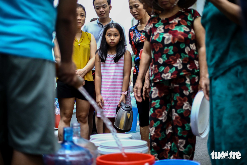 Children help their parents carry clean water in Hanoi. Photo: Nguyen Khanh / Tuoi Tre