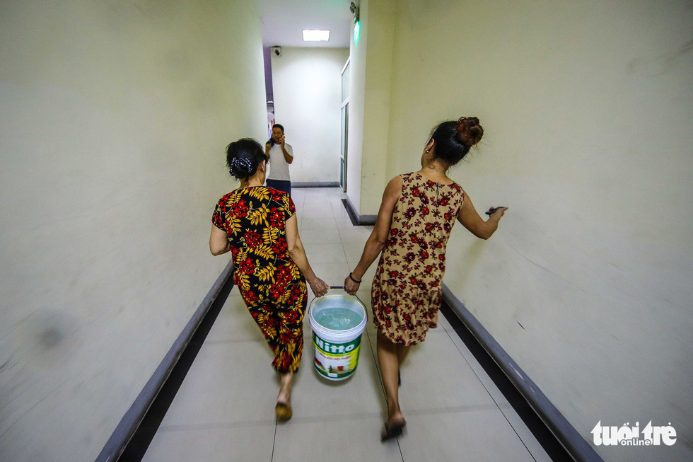 Two women carry a bucket of fresh water back to their apartment in Hanoi. Photo: Nguyen Khanh / Tuoi Tre