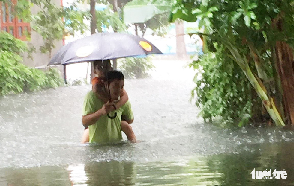 A man carries his son on his back as he walks through a flooded area in Vinh City.