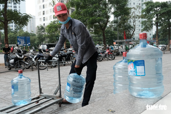 A man delivers bottled water to his buyers. Photo: Mai Thuong / Tuoi Tre
