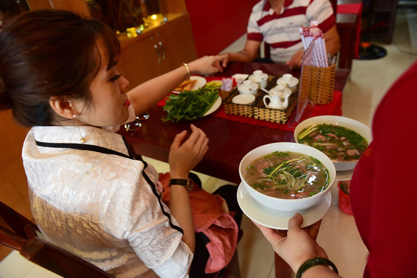 A waiter serves two bowls of pho at Pho Ngoc Linh. Photo: Quang Dinh / Tuoi Tre