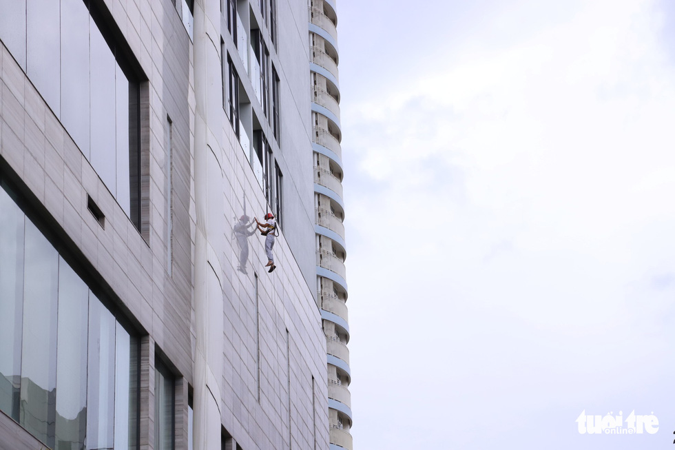 A man practices escaping from a building with a rope during the fire drill in Da Nang, Vietnam, October 16, 2019. Photo: Doan Cuong / Tuoi Tre