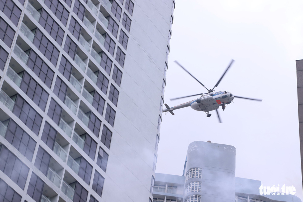 A helicopter hovers above a building during the fire drill in Da Nang, Vietnam, October 16, 2019. Photo: Doan Cuong / Tuoi Tre