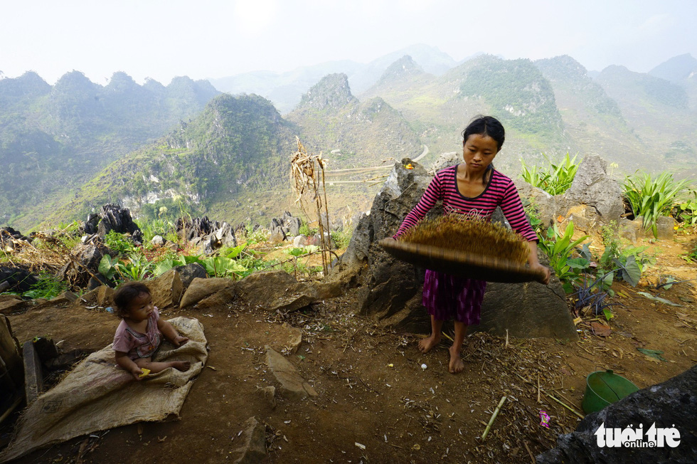 A woman does household chores while her child sits nearby in Dong Van District, Ha Giang Province, Vietnam. Photo: Quang Dinh / Tuoi Tre