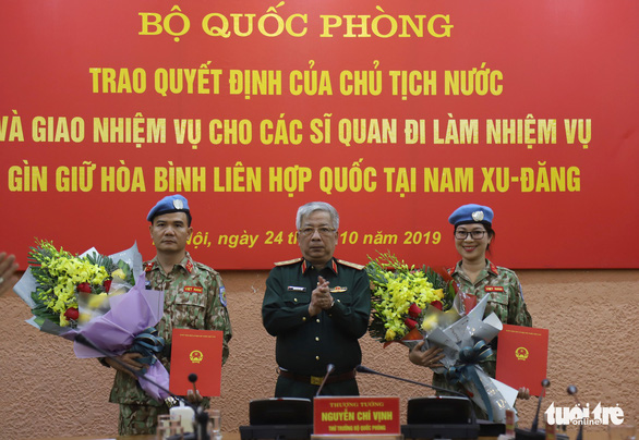 Vietnamese Deputy Defense Minister Sen. Lt. Gen. Nguyen Chi Vinh present UN peacekeeping dispatch orders to Sen. Lt. Col. Le Ngoc Son (L) and Maj. Nguyen Thi Minh Phuong at a ceremony in Hanoi on October 24, 2019. Photo: Danh Trong / Tuoi Tre