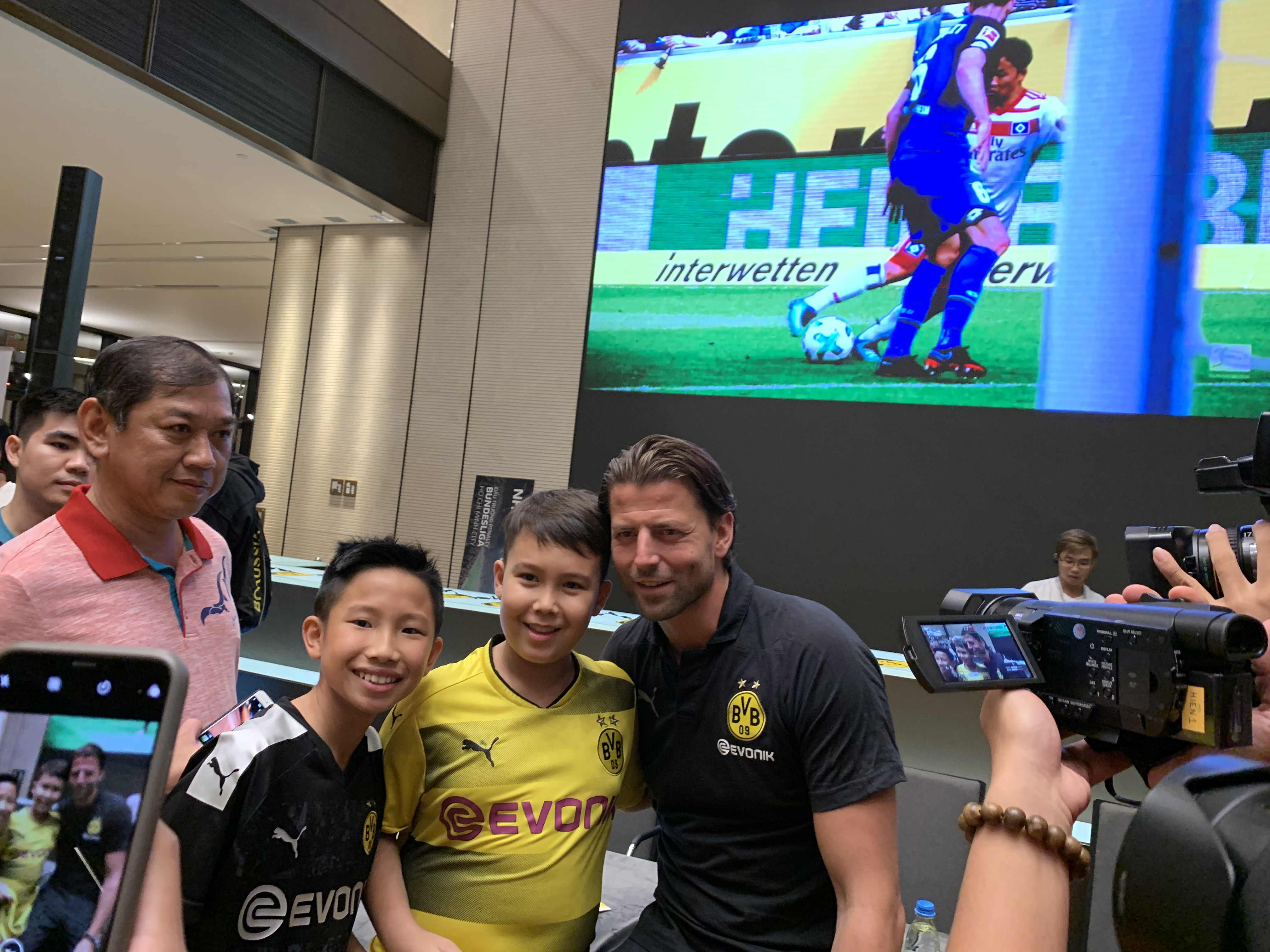 Germany's goalkeeper Roman Weidenfeller takes a photo with fans. Photo: Bao Anh / Tuoi Tre News