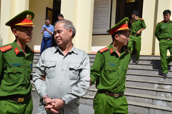 Dinh Bang My, 58, is escorted out of the courtroom by two policemen in Phu Tho Province, located in northern Vietnam, October 29, 2019. Photo: Giang Long / Tuoi Tre