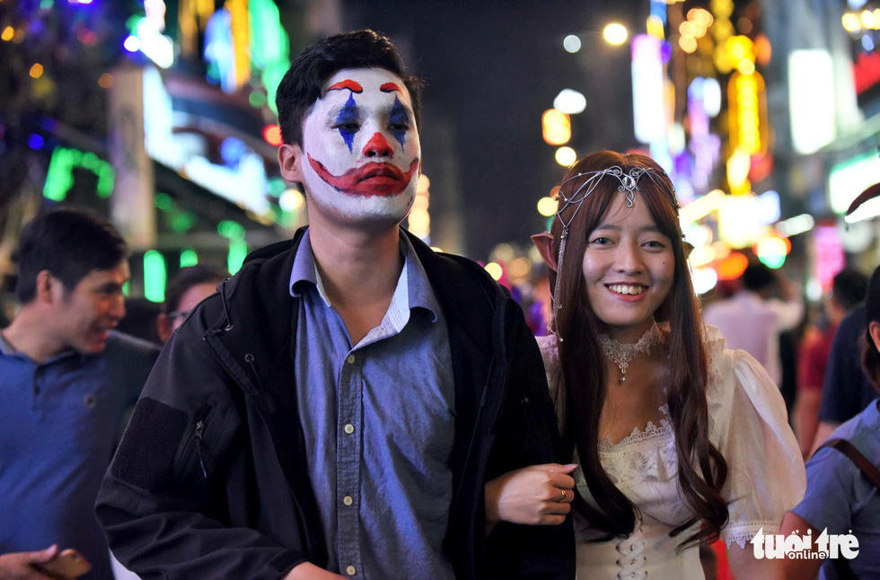 A man masquerades as a clown alongside a woman dressed as a beautiful goblin on Bui Vien Street in District 1, Ho Chi Minh City, October 31, 2019. Photo: Duyen Phan / Tuoi Tre