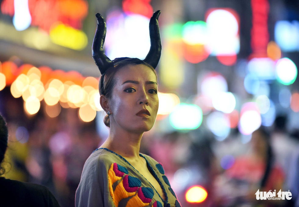 A woman makes her best attempt at recreating Maleficent, a Disney's character, on Bui Vien Street in District 1, Ho Chi Minh City, October 31, 2019. Photo: Duyen Phan / Tuoi Tre