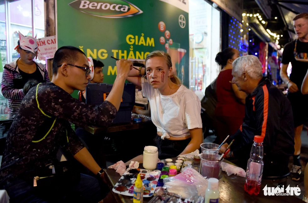 A man offers make-up service to a British woman on Bui Vien Street in District 1, Ho Chi Minh City, October 31, 2019. Photo: Duyen Phan / Tuoi Tre