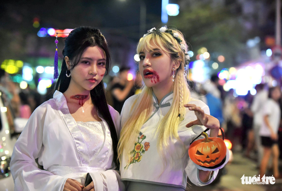 Two women show creepy costumes and macabre make-up on Bui Vien Street in District 1, Ho Chi Minh City, October 31, 2019. Photo: Duyen Phan / Tuoi Tre