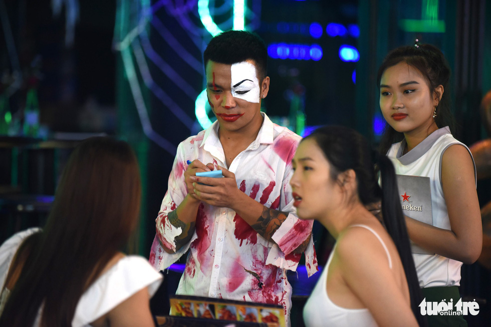 A restaurant waiter wears a bloodied shirt and morbid make-up on Bui Vien Street in District 1, Ho Chi Minh City, October 31, 2019. Photo: Duyen Phan / Tuoi Tre