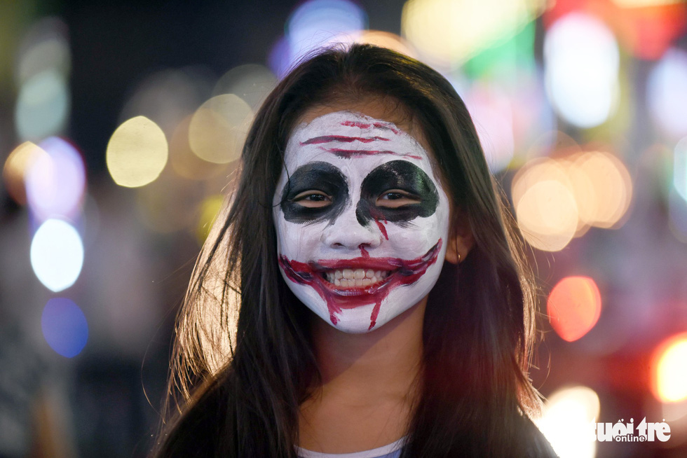 A woman shows off her horror-themed face paint on Bui Vien Street in District 1, Ho Chi Minh City, October 31, 2019. Photo: Duyen Phan / Tuoi Tre