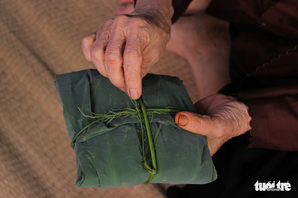 Nguyen Thi Can wraps green sticky rice inside the lotus leaf at her house in Hanoi. Photo: Ha Thanh / Tuoi Tre