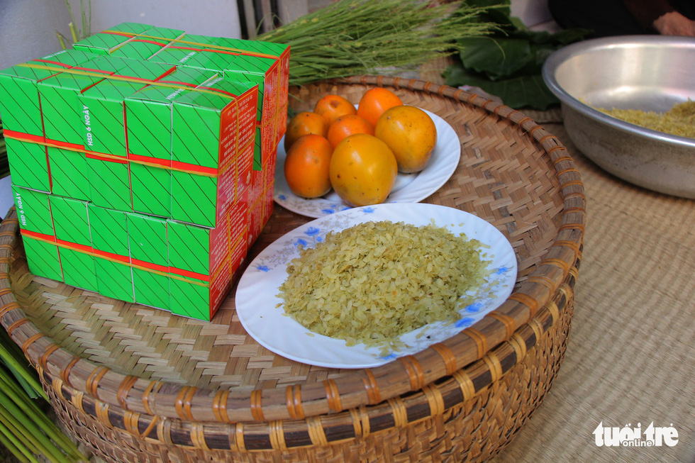 Green sticky rice is placed onto a plate along with Hanoi's signature green sticky rice cakes and Vietnamese peaches. Photo: Ha Thanh / Tuoi Tre