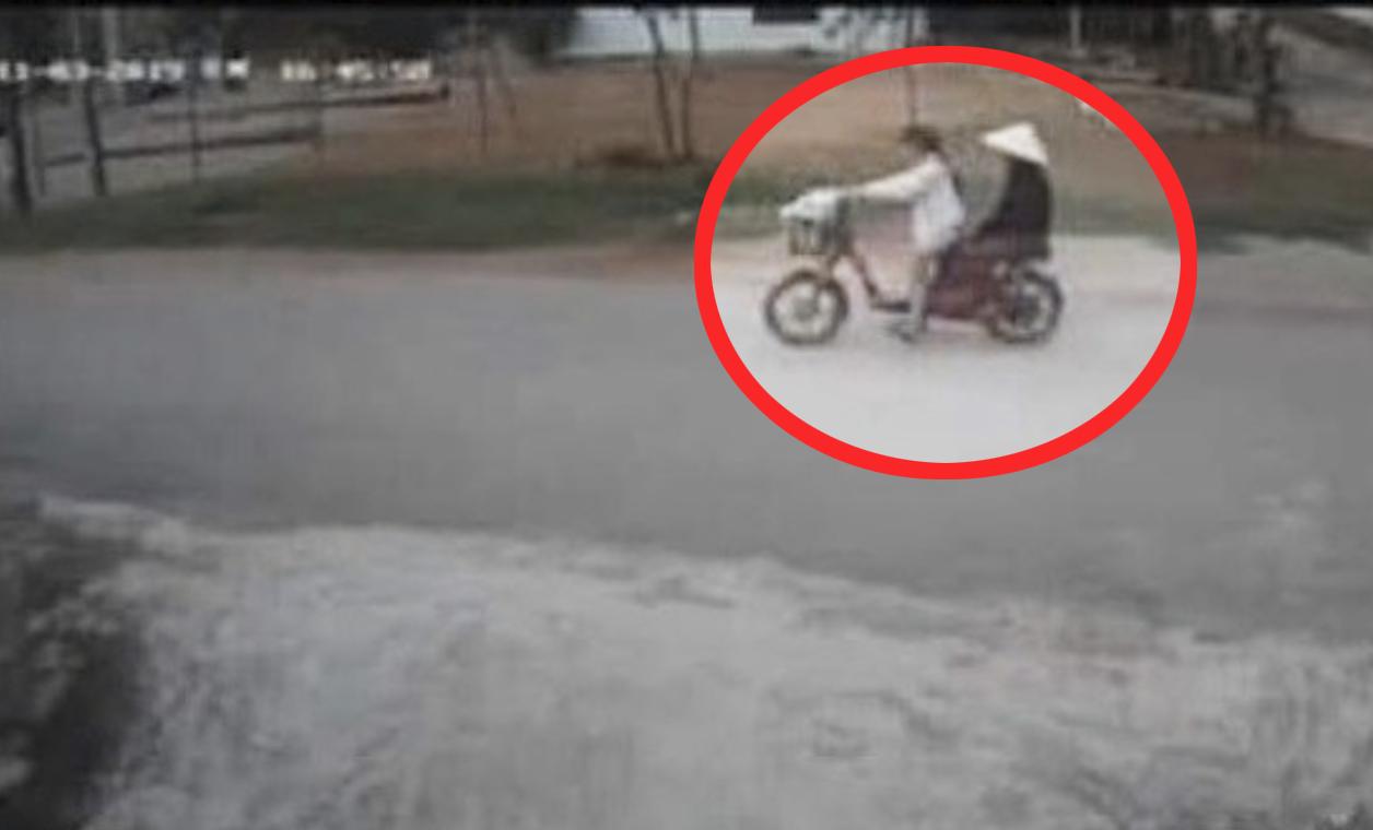 T. carries her grandmother on an electric bike towards Bau Ganh dam Photo: K.Kien / Tuoi Tre